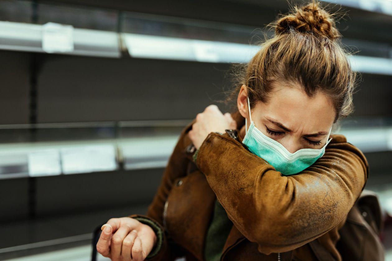 Mujer con mascarilla estornudando en el codo. DRAZEN ZIGIC/ISOCK